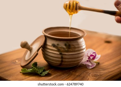 Honey in a Jar, liquid honey with honey stick spoon dripping honey and shot from above, on a wooden background