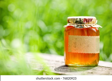 Honey jar on table against nature background. Shallow depth of fields