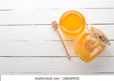 Honey in a jar on a white wooden background. Free space for text. Top view.