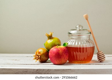 Honey jar, red apples and pomegranate on white wooden board