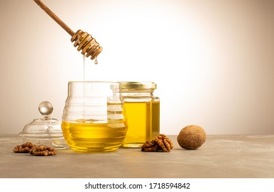 Honey in a jar with ripe walnuts and wooden dipper.Healthy and antivirus food.