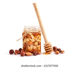 A honey jar with a spoon for honey and different nuts on white background