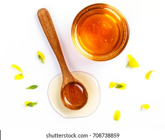 Honey with jar and honey spoon and flower isolated on white background