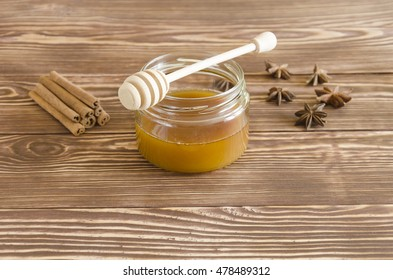 Honey jar and honey stick with spices on a wooden background.