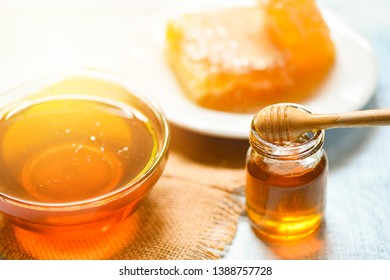 Honey in jar with wooden dipper and honeycomb on white plate on table background