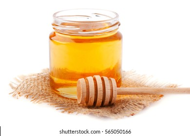 Honey in jar with a wooden spoon isolated on white background