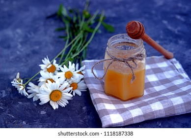 Honey in a jar, wooden stick and a bouquet of chamomiles