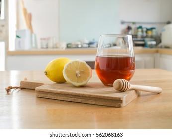 Honey lemon - lemon on chopping board and Glass of honey and honey dipper on wooden table