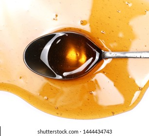Honey and metal spoon isolated on white background, top view