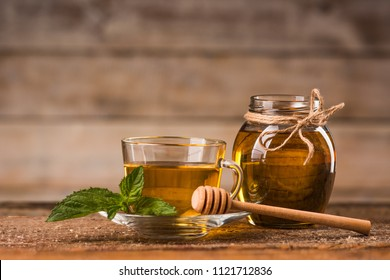 Honey and mint tea on a wooden background