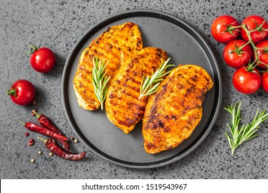 Honey mustard grilled chicken breasts, cast iron skillet, dark background. Top view.