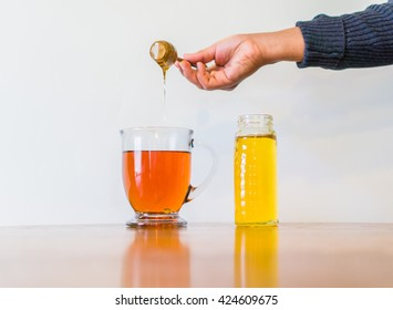 honey, an natural antiseptic sweetener, being dripped into a hot cup of tea  with a wooden dipper