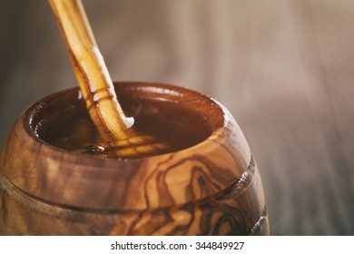 honey in olive wood pot with dipper on table, vintage toned