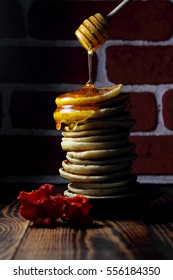 Honey and pancakes on a wooden table