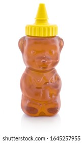 Honey in plastic dose, which is shaped like small bear. Isolated on white background with shadow reflection. With clipping path. With vector path. Copper in plastic bear shaped container, on white bg.