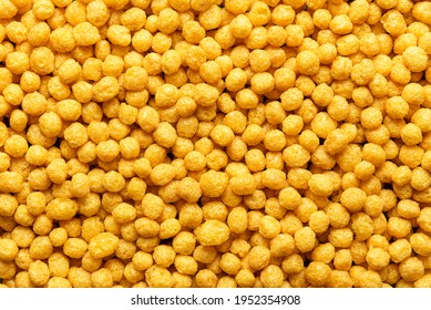 Honey pops breakfast cereals background, flat lay. Full frame with cornflakes. Delicious corn cereal balls. Macro image with yellow round cereals.
