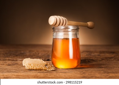 Honey pot preserved with honeycomb on wood background