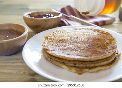 Honey pouring over a stack of pancakes. Snack of pancakes accompanied by bowls of jam on rustic wooden table.