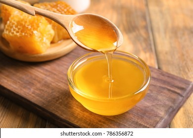 Honey pouring from spoon into glass bowl on table, closeup