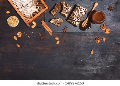Honey products background. Honeycomb frame, bee pollen granules, honey in glass pot, almond nuts on black slate tray over dark background. Copy space. Top view. Autumn harvest concept