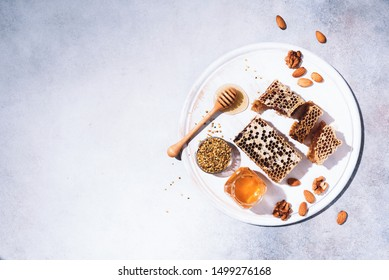 Honey products background. Honeycomb frame, bee pollen granules, honey in glass pot, almond nuts on grey concrete background. Copy space. Top view. Autumn harvest concept. Banner.