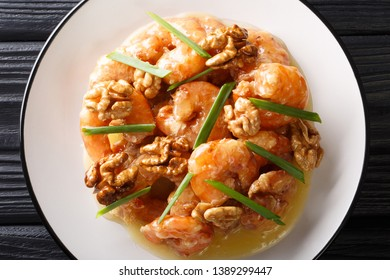 Honey Shrimp are fried with a tempura batter and quickly tossed in a honey sauce and sweetened walnuts close-up on a plate. horizontal top view from above