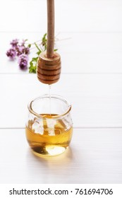 Honey in a small glass jar on a white table Honey dripping from dipper