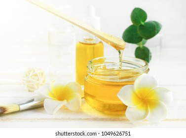 Honey spa treatment. Pouring sweet golden honey to jar, plumeria flowers, soft sunny light. Natural homemade skincare