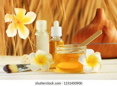 Honey spa with tropical flower frangipani decor, jars with golden beauty treatment oils for relaxing skin care under straw thatch.