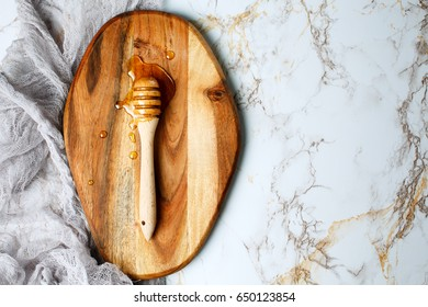Honey spoon, special wooden dipper for liquid honey product close-up on a marble background