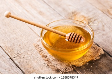 Honey and honey sticks in a glass bowl
