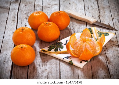 Honey tangerines whole and one peeled, on antique wooden table.