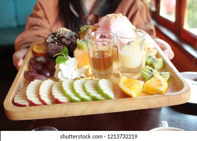 Honey Toast, composed with scoops of strawbery and chocolate ince cream, is served with variety of fruits including apples, kiwi, grapes, bananas, topped with pepermint, arranged on a wooden tray