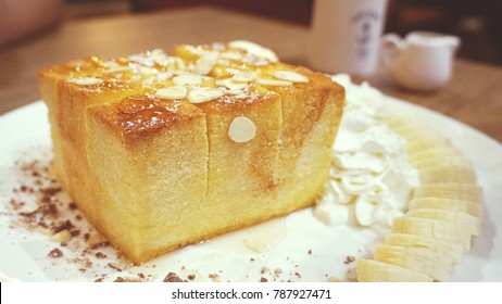 Honey toast topping by almond slice with whipping cream and banana, selective focus