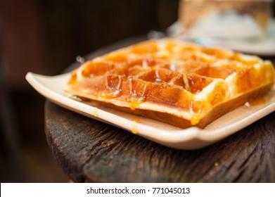 Honey Waffle Put On white Plate,honey waffle lay on white plate put on wooden table,delicious honey waffle