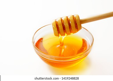 Honey with wooden honey dipper.
