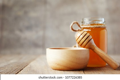 Honey and wooden honey dipper on wooden background.