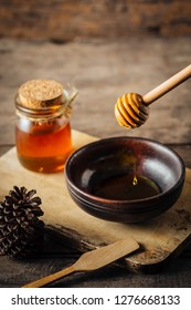 honey with wooden dipper on wooden background