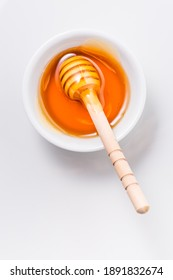 Honey with wooden honey dipper on white background