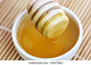 Honey with wooden honey dipper and white bowl
