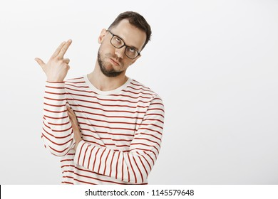 Honey, your talks killing me. Portrait of bored annoyed funny european man in glasses, rolling eyes and making gun gesture near head as if shooting himself and committing suicide from boredom