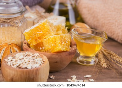 Honeycomb, cosmetic oil, sea salt, oat and handmade soap with honey on rustic wooden background. Natural ingredients for homemade facial and body mask or scrub. Healthy skin care. SPA concept.