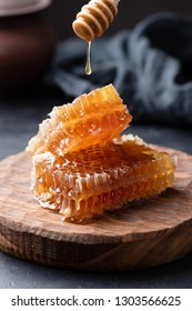 Honeycomb and honey dipper with liquid honey. Selective focus