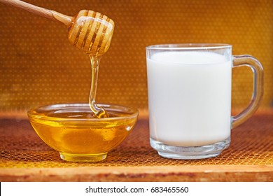 Honeycomb and honey in glass bowl, milk with wood stick