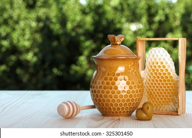 honeycomb and honeypot on a background of trees