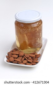Honeycomb in jar with raw almonds on plate