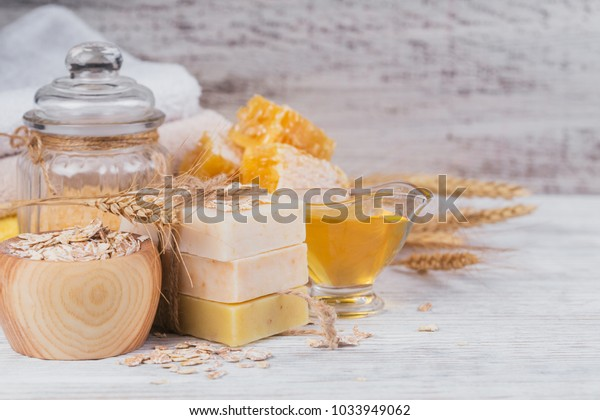 Honeycomb, sea salt, oats and handmade soap with honey on white rustic wooden background. Natural ingredients for homemade facial and body mask or scrub. Healthy skin care. SPA concept.