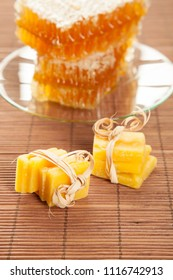 Honeycombs and beeswax on bamboo background