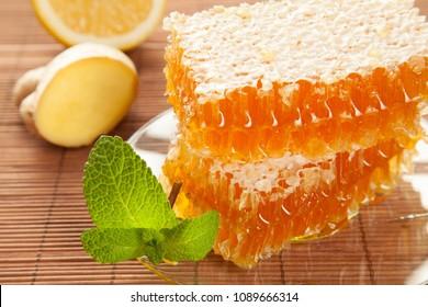 Honeycombs, ginger, lemon and fresh mint on bamboo background
