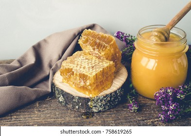 Honeycombs and glass pot with honey on old wooden table with purple flowers.